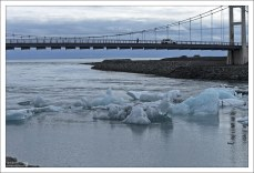 Плотина из каменных валунов предотвращает эрозию опор моста.