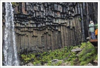 Водопад низвергается на фоне базальтовых столбцов.