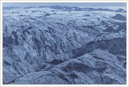 Еле видимая цепочка людей потерялась среди массы ледника.
