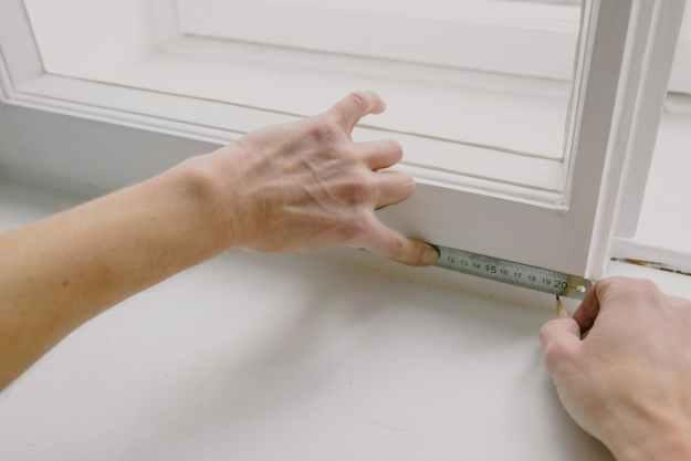 crop worker measuring window frame with ruler