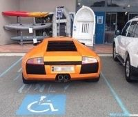 Lamborghini laranja estacionada em vaga para deficientes