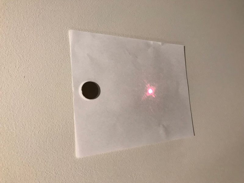 Laser dot reflects off of piece of paper held to wall by magnet