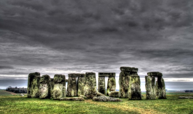 Stonehenge. An enhanced photograph of this iconic UK landmark. A lowering sky, striking Pembrokeshire blue stones covered in moss, lush green grass and hills in the distance. © Copyright 2014 Andy Huntley photography
