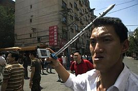 A Han Chinese man carries a spiked steel bar while using his cell phone to take photos as he joins a mob attacking Uighur properties in Urumqi, July 7, 2009 (AP Photo/Ng Han Guan)