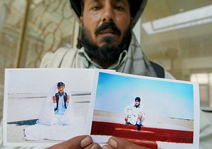 A relative of Mohamed Jawad holds up photos of Jawad, taken shortly before his capture