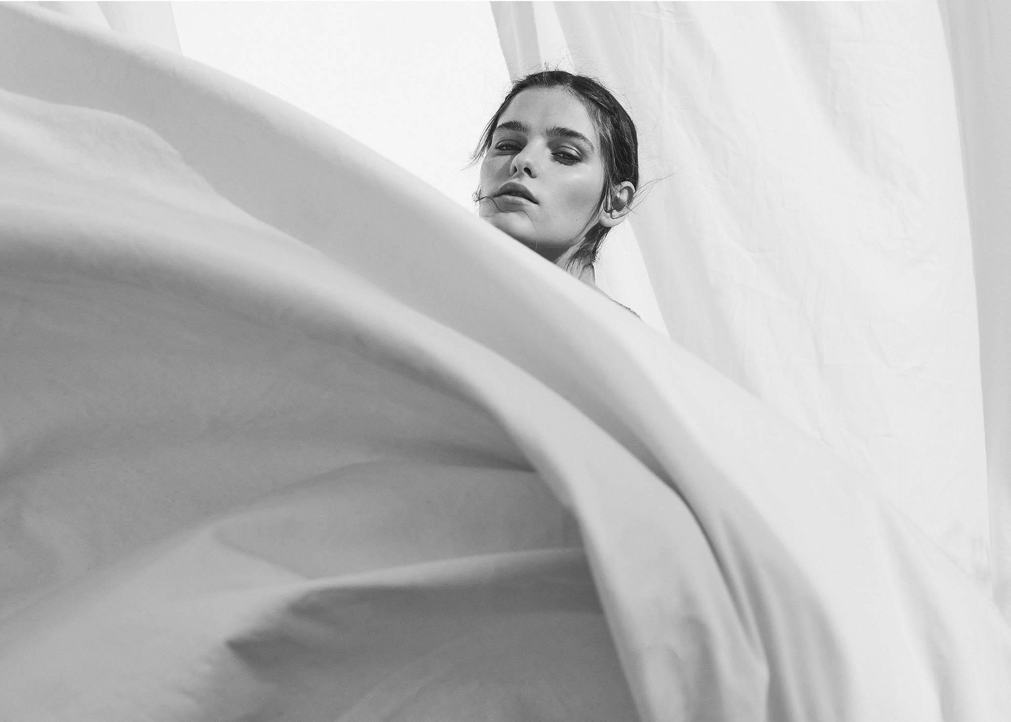 Stradivarius fotografía comercial chica entre telas blancas