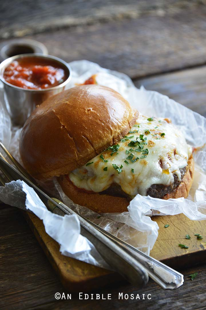 Pizza Burger with Vintage Knife and Fork on Wooden Board with Chunky Marinara Sauce