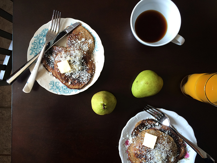 Paleo pancakes topped with coconut, plus pears, fresh orange juice, and coffee.