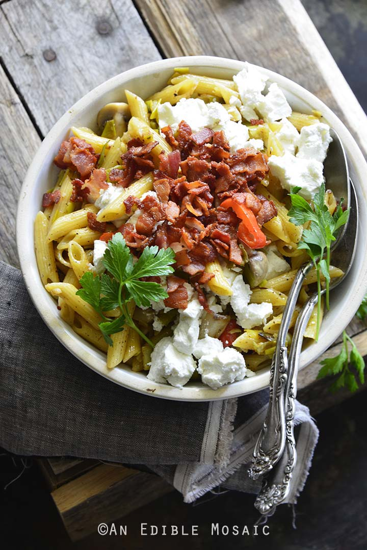 Warm Caramelized Leek Pasta Salad with Bacon and Goat Cheese on Wooden Background Front View