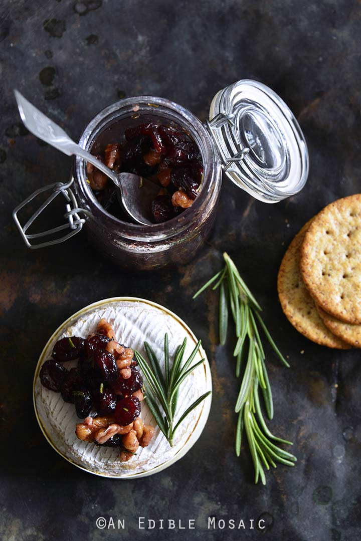 Baked Goat Brie with Spiced Rosemary-Scented Honey and Red Wine Cranberries Overhead View with Crackers