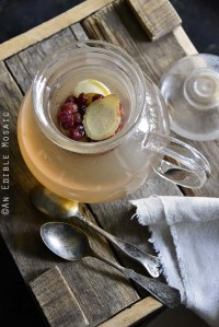 Pot of Honey-Apple Cranberry Ginger Tisane on Wooden Crate