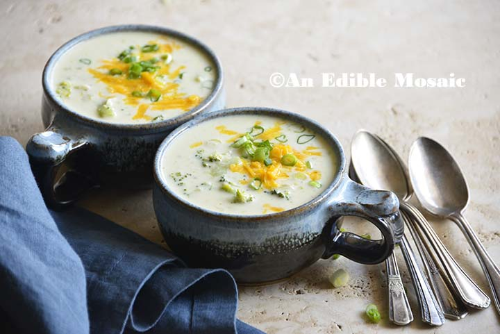 Keto Broccoli Cheese Soup in Blue Mugs with Dark Blue Linen