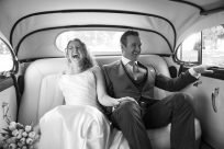 bride and groom laughing in a vintage car