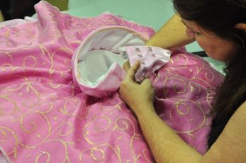 A woman does hand needlework on a pink satin gown.
