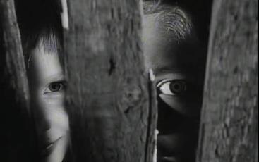 Photo by Margaret Sang - children peek through the gaps