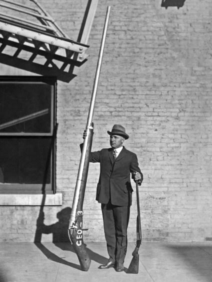 Hombre mostrando una punt gun en comparación a una escopeta normal.