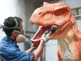 Operario de la fábrica de dinosaurios pintando un traje de dinosaurio.