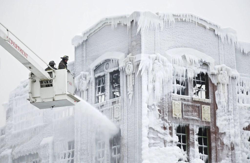 Fotografía de dos bomberos apagando un invendio durante el invierno.