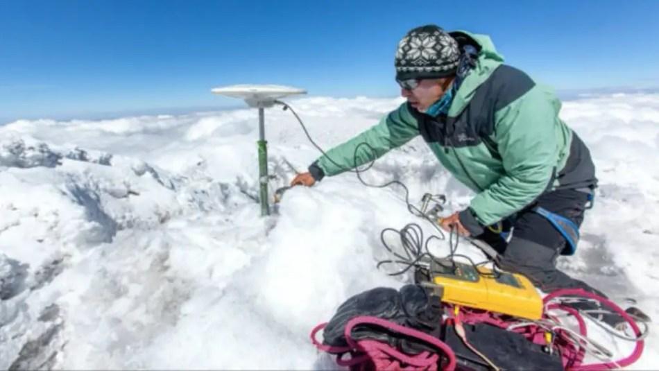 Investigador meteorológico instalando equipos de medición atmosférica en la cima del volcán Chimborazo.