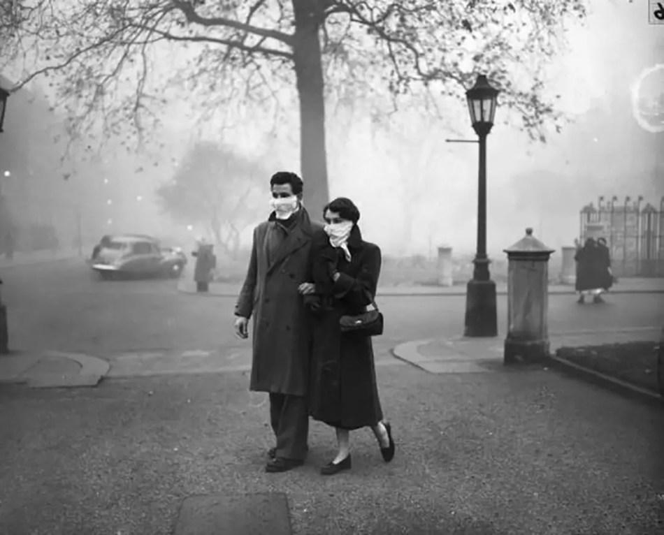 Pareja caminando entre la contaminación londinense causada por el Great Smog.