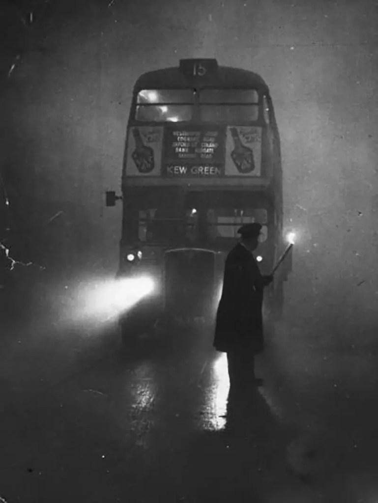 Transporte público londinense cubierto por una intensa capa de smog causada por el Great Smog..