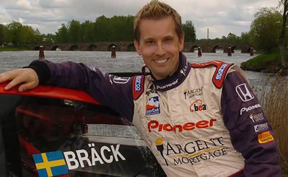 Kenny Bräck posando junto a uno de sus automóviles de carrera.