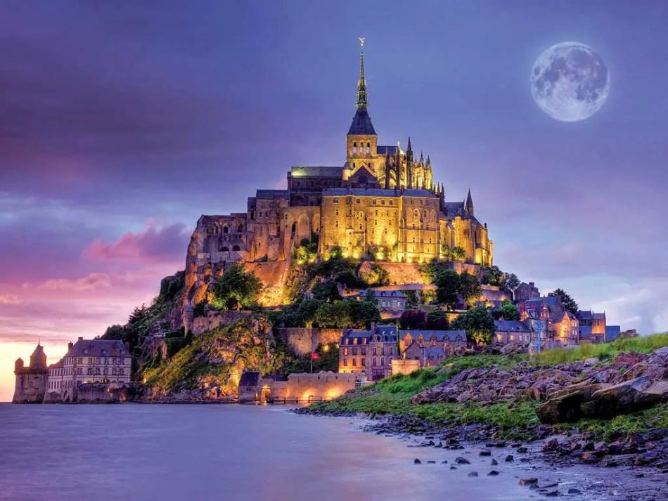 El Monte Saint-Michel durante la noche con la luna llena de fondo.