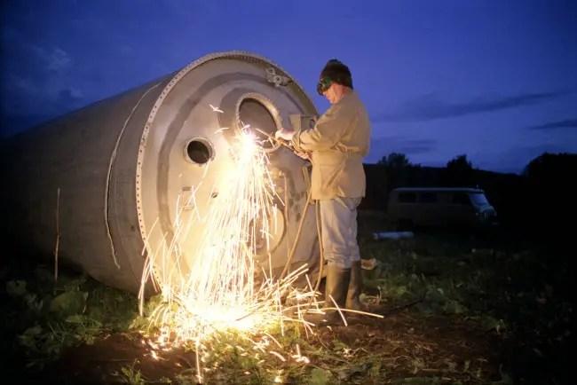 Poblador de la región de Altái cortando los restos de un cohete para su venta.