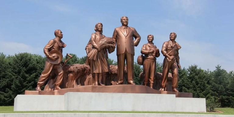 Estatua del dictador comunista norcoreano Kim Il-sung junto a un grupo de trabajadores norcoreanos.