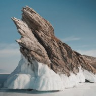 rock on icy sea under blue sky in winter