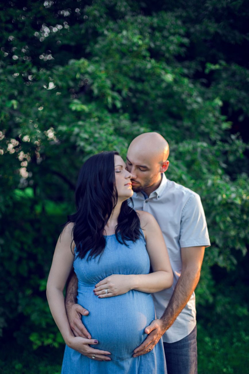 Maternity portrait of a couple kissing and hugging each other