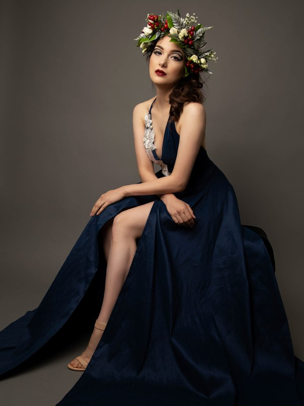 Caucasian model wearing a long royal blue gown and a winter themed flower crown