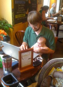 Angela's husband working from a coffeeshop with our first-born as a baby.