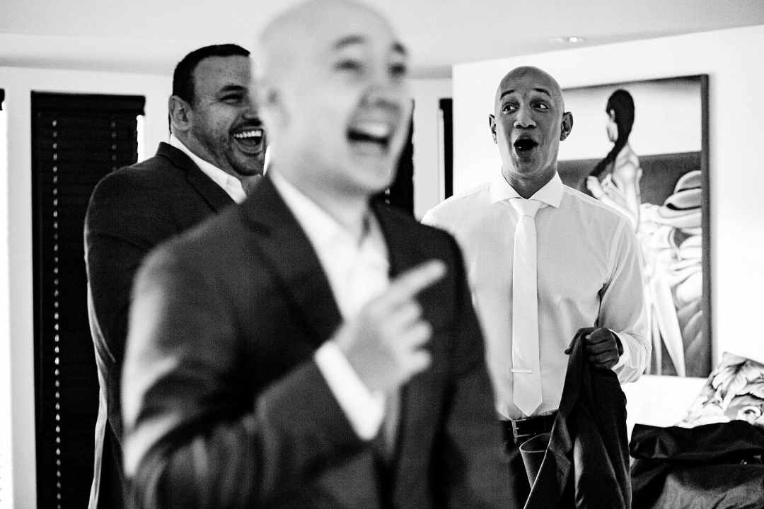 candid shot of groom laughing with best man