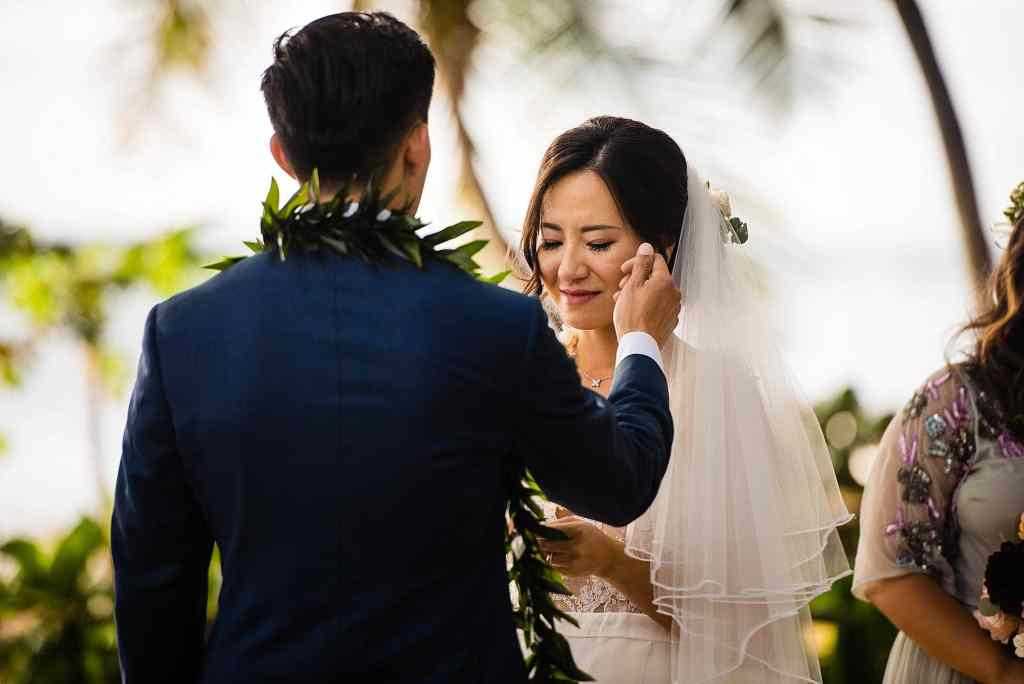 groom brushing bride's cheek during ceremony