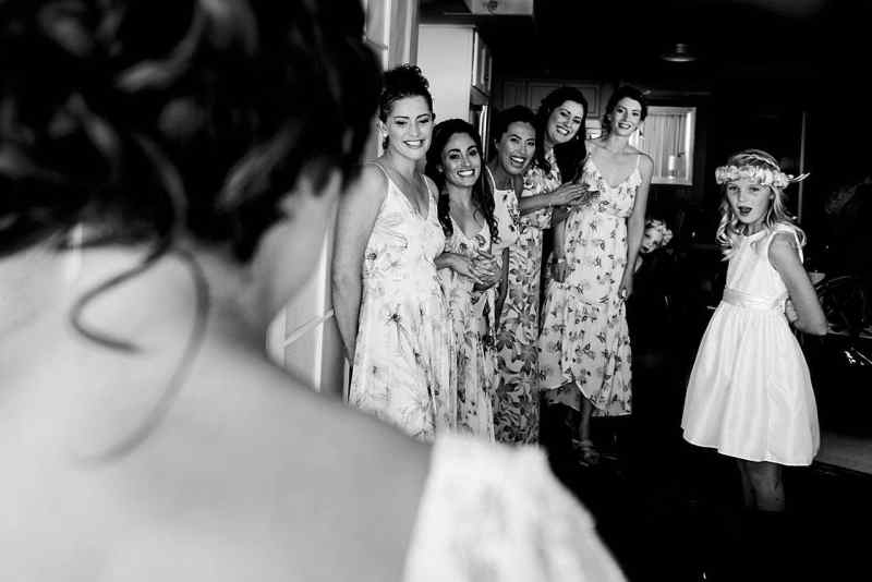 bridesmaids reacting to bride in her dress