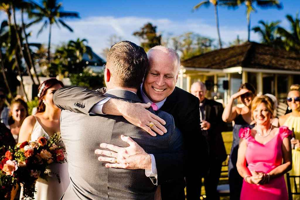 father of the bride hugging groom at white orchid beach house