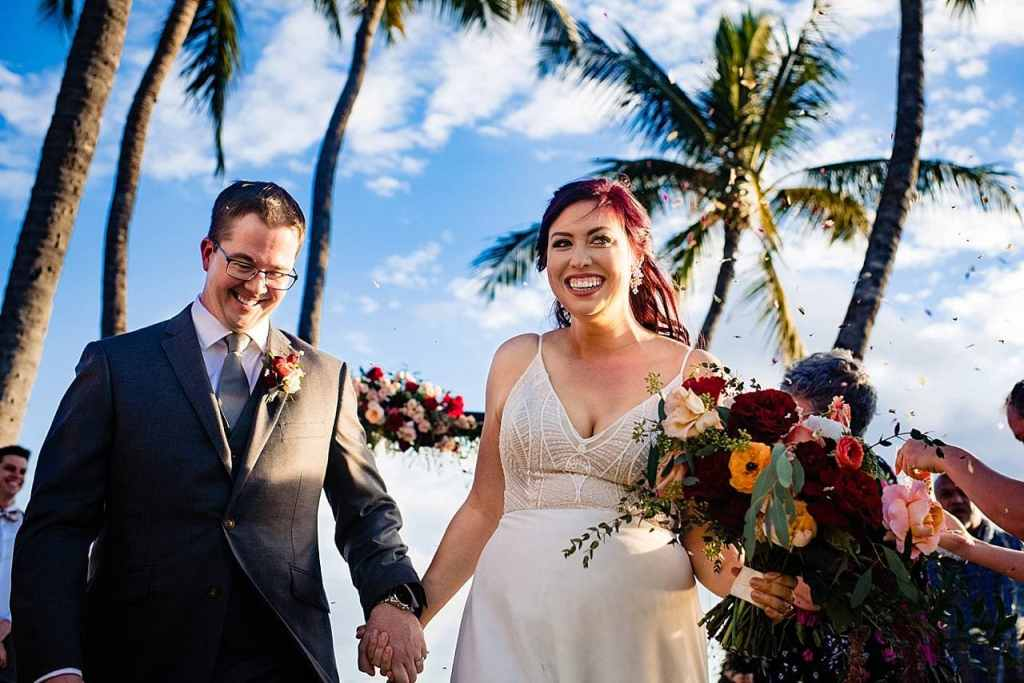 bride and groom walking back down the aisle at white orchid beach house wedding in maui