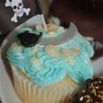 vanilla cupcake, blue and white butter icing, sugar paste, fondant cutlass, gold coins, pirate theme