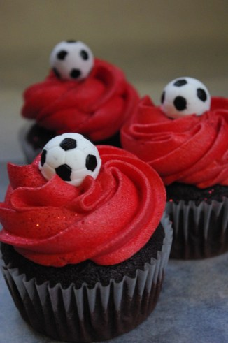chocolate cupcakes, red vanilla butter icing, sugarpaste soccer balls