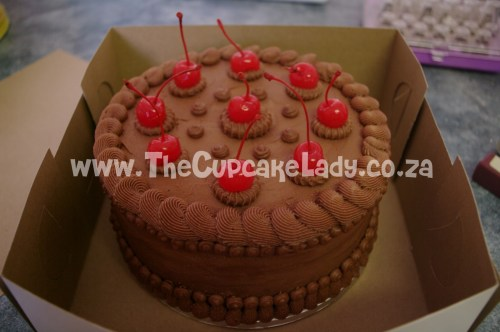 chocolate cake filled with caramel covered with chocolate butter icing decorated with Maraschino cherries