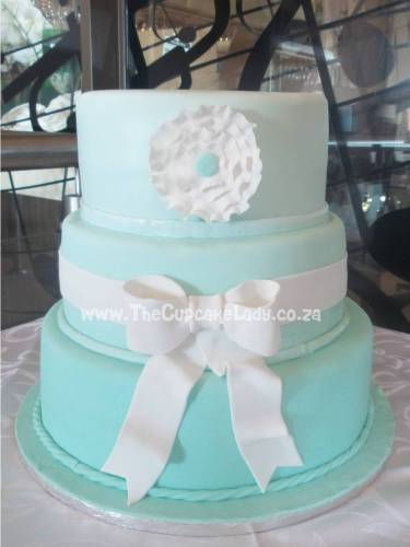 Wedding cake, mint green ombre tiers with a bow and a stylised flower