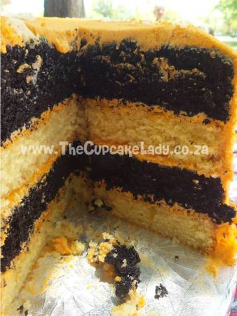 Midrand cake artist, cupcakes, cakes and sugar art. Layers of chocolate and vanilla cake with bright orange buttercream. The chocolate cake is coloured black!