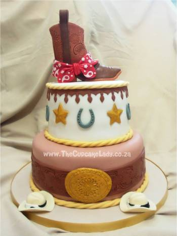 "Cake artist Midrand. Cakes, cupcakes, sugar art. Custom made. Hand made. Sugar paste cowboy boot cake topper with red bandanna. Two-tiered wild West rodeo-themed cake, vanilla cake top tier, chocolate cake bottom tier, decorated with a tooled ""leather"" belt and buckle, stars, horseshoes, little stetsons, and rope."