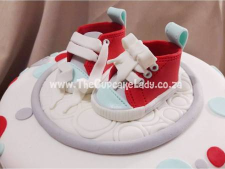 Cake artist Midrand. Cakes, cupcakes, sugar art. Custom made. Hand made. Sugar paste baby sneakers cake topper, in a red, grey and sky blue colour scheme.