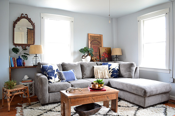Light blue living room with gray couch and bohemian accents