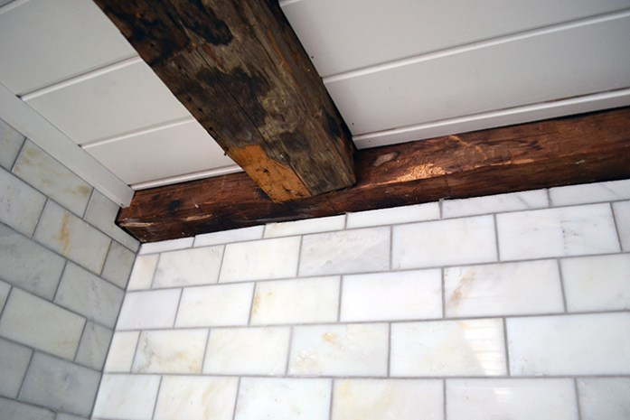 Bathroom renovation using marble subway tiles for a shower surround to complement old wood beams.