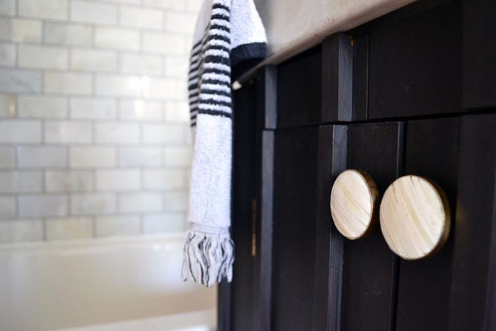 Stone and Gold cabinet knobs from Hobby Lobby contrast against the dark painted vanity in this bathroom renovation.