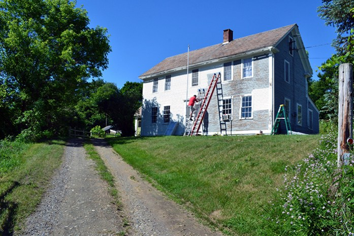 Scraping and painting the exterior clapboards of an old colonial farmhouse