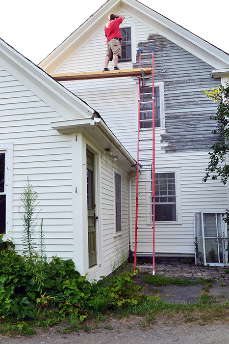 Setting up DIY ladder staging to help paint house exterior